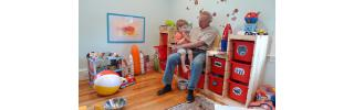 Toddler boy and grandfather sit talking in a playroom